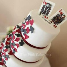 A gorgeous 4 tier wedding cake with a 'classy vegas theme' burgundy and charcoal grey sugar card suits cascade down the cake like confetti with the king and queen of hearts on top.