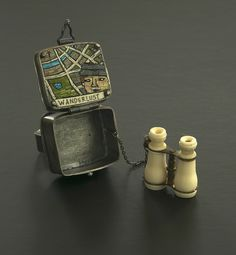 The Wanderlust ring done in 2014 opens to reveal a map mosaic and a miniature pair of binoculars we found at Curtis Steiner's shop in Ballard. If you peer through the binoculars you see images of two cities (though I don't remember which ones!).