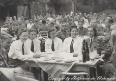 Helferin dining outside with several officers and other soldiers.  White uniform shirts were only worn on special occasion dress guidelines.