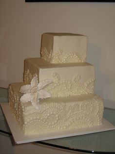 3 tier square wedding cake with hand piped beading and a gumpaste lily.