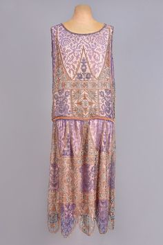 BEADED SILK and METALLIC LACE DRESS 1920s Lavender lace decorated with silver beads, having inserts of metallic gold lace decorated with peach, coral and turquoise beads, sleeveless boatneck bodice with dropped waist and scalloped hem, peach silk underdress. - whitakerauction