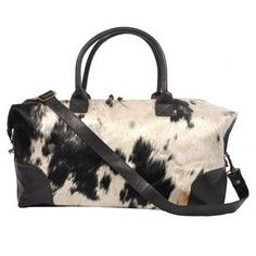 Handcrafted cowhide duffle with leather trim and a removable shoulder strap.