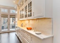 A kitchen in Chicago was remodeled and taken to new heights with Fieldstone Cabinetry's Geneva inset door style. This kitchen has two Fieldstone Cabinetry colors: Marshmallow Cream on Maple for the perimeter cabinets and Slate on Maple for the island. The kitchen is super functional with ample storage space, as well as an impromptu dining area incorporated into the island. Tina Yarbrough designed this kitchen. She is a designer for B&C Interiors, a Fieldstone Cabinetry dealer in Elgin…