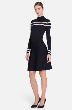 Crisp white stripes add chic drama to a lightweight sweater-knit dress fitted with a wide inset waistband before flaring to a full A-line skirt. A mock neck and long sleeves frame the striking style.