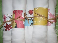 Scrapbook Paper Napkin Rings - I would use scalloped scissors to trim them and embellish with a flat pearl over the twine. Would be so cute, reasonable, tailored to your colors, and can be done well in advance.  I did something similar for a beachy birthday party (with burlap, twine, shells, seahorses, etc)