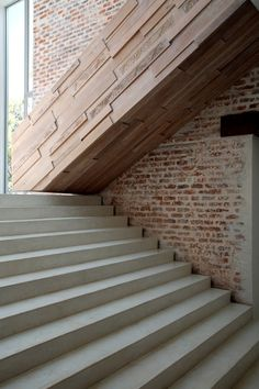 A textured and mannered wood stair is inserted against smooth concrete steps and a rough brick wall by architects Silvio Rech and Lesley Carstens.