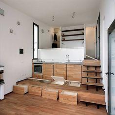 Interno casa cucina, con il pavimento che si trasforma in un contenitore di oggetti per razionalizzare il piccolo spazio a disposizione