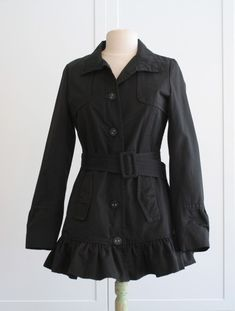 she cut off the bottom of a longish trench coat and put ruffles on it!  Excellent!