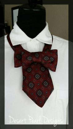 Are you looking for a statement piece to add to your wardrobe? Look no further! This necktie necklace is made from an upcycled mens silk tie. The fabric features intricate patterns of burgundy, red, navy blue, sky blue, and tan. The tie easy to use because of the snap closure that