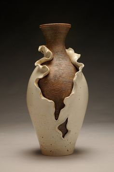 """Vanessa Quintana  Unfurling Vase, glazed ceramic pottery  Ceramic, high-fired, glazed with black and red iron underglaze washes and spodumene (cream-colored high-fire glaze with iron flecks).Dimensions: 18"""" tall x 9"""" wide x 9.5"""" wideWeight: 20 lbsThe idea behind this is the shedding of skin to reveal the raw, natural state that lies within the boundaries and expectations of the traditional vase form."""