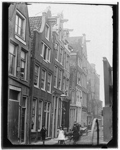 Buiten Dommersstraat 2-18 | 1892 |   Dommersstraat (Buiten) 2 t/m 18 (v.r.n.l.). Gezien naar Haarlemmer Houttuinen. Nr. 16 was tot 23 oktober 1891 de woning vanGerbrand Kost, sinds 5 april 1891 weduwnaar van Maria Olie. Links: Jan Olie,rechts: Jacob Olie jr. Midden: onbekend meisje (Miep Kost?)