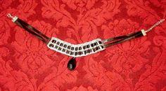 Ho realizzato questo collarino intrecciando linguette di lattine con un nastrino nero, l'ho abbellito con un pendente centrale costituito da una finta pietra nera sfaccettata,                terminandolo infine con una chiusura estendibile. (15 euro) By Re-Trash Up Bazaar                                                           VENDUTA!