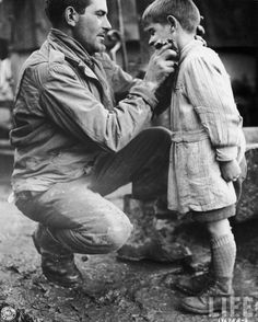 American soldier cleaning the face of young French orphan.