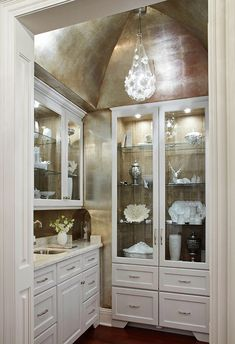 Silver leaf walls and a cove ceiling make this butler's pantry shine! (Traditional Home magazine)