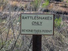 A passive-assertive sign warning people to stay out of an area because of the danger of rattlesnakes. Rattlesnakes only beyond this point.