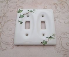 """fabulous vintage 1980s white ceramic double toggle switch plate cover embellished with sweet green ivy motif - no mounting screws - perfectly gorgeous for your cottage shabby decor and lovely in your kitchen Size - 4 5"""" long x 4 5"""" wide (measured at widest points) Weight - 232gms Circa - 1980s/90s Origin /  Label - no makers mark Condition - excellent, gently used"""