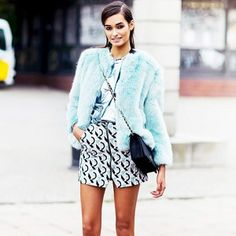 A teal fur coat is paired with a bright patterned skirt, metallic blouse and black cross-body bag.