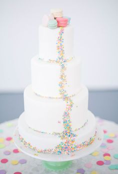Sprinkle Wedding Cake with Macaroons. What's even better than a sprinkle wedding cake? A sprinkle cake topped with a cute quintet of macaroons! This confection, created by Sweet Celebrations Wedding Cakes, is the definition of a delectable treat.
