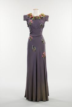 "Embroidered purple silk ""Pagan"" evening dress with silk flowers, by Elsa Schiaparelli, French, fall 1938. This enchanting evening dress is from Schiaparelli's fall 1938 Pagan collection, which was inspired by Botticelli's paintings. For this collection, evening gowns were cut in a slim silhouette and ornamented with embroidered foliage and, as in this case, plastic leaves and flowers. As Dilys Blum asserts in ""Shocking! The Art and Fashion of Elsa Schiaparelli,"" this gown is inspired by Flora..."