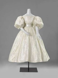 1835 Wedding gown of white silk gauze with a woven white satin flower and border pattern, with two for each winding flowers and vines, from wavy S scrolls