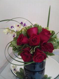 bello diseño de Rosas rojas con un delicado toque de Orquideas