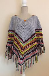 """This blanket poncho crochet pattern, or """"ponchet"""" as I like to call it, is made by working rounds, increasing on the corner to make sure that it stays flat so it is usable as a blanket. The square in the centre is buttoned in place allowing it to be removed so the ponchet can then be slipped over the head and worn."""