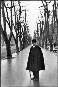 henri cartier bressonFRANCE. 1932. - FRANCE. Marseille. The Allée du Prado. 1932.  I was walking behind this man when all of a sudden he turned around.      - Bare tree, Bowler hat, Cigarette, Exterior, Man (all ages), Marseille, Pavement, Perspective, Smoker, Symmetry, White people