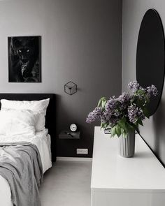Black Panther poster on grey wall in cozy bedroom above bed and with purple flower decoration