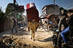 A man carried a sofa suspended from a rope over his forehead in Katmandu, Nepal, on Monday. (Agron Dragaj/Zuma Press)