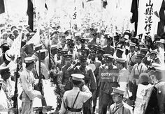 Photo shows General Chiang Kai-shek, Commander in Chief of the Nanking Nationalist forces, passing through a crowd of admirers at Hsuchowfu, where a treaty was arranged with General Feng Yu-hsiang, the Christian General, to drive the Communists out of China. Ceneral Chiang is saluting and facing the camera.