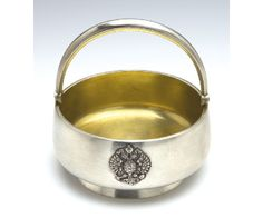 A FABERGE SILVER SUGAR BOWL, MOSCOW, 1908 -1917 the circular low bowl with plain sides with applied armorials and on circular foot, tapered handle, gilt interior, struck in Cyrillic beneath the Imperial Warrant, 84 standard.