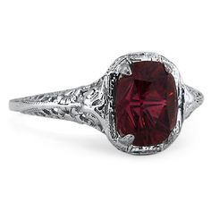 A stunning, burgundy colored center gem is enhanced by an intricately detailed filigree setting of precious metal (approx 1.90 ct. tw.).