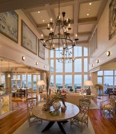 The dramatic two-story great room in this beach house features massive floor-to-ceiling windows to admit a stunning ocean view