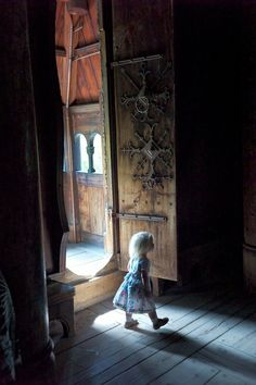 Child walking in the light of a Stavechurch door in norway
