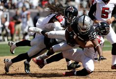 Oakland Raiders' Taiwan Jones (22) is tackled by Atlanta Falcons' Philip Wheeler, rear, and Eric Weems during the first half of an NFL football game in Oakland, Calif., Sunday, Sept. 18, 2016.