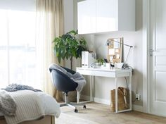 A white desk with a black swivel chair on castors and a wall cabinet, inside the bedroom. | Workspace