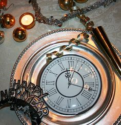 New Year's table - Printed clock faces placed between silver chargers and clear glass plates are the foundation for the place settings.