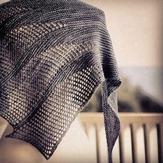 """Inspired by subterranean waterways, """"Artesian"""" is a triangular shawl with asymmetrical sections of lace spilling over the shawl's edge."""