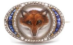 "circa 1900 brooch that contains an ""Essex"" or reverse crystal. A fox intaglio was carved into the back of the crystal cabochon and then painted"