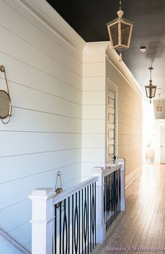 Shiplap brings charm to the staircase and hallway. Colors: Shiplap Walls: Alabaster by SW, Ceiling- Inkwell by SW.