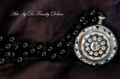 This is a gorgeous diorama piece, made from an antique pocket watch and 24 inches of jet black glass pearls, carefully strung together in a rosary style. A sterling silver clasp holds it all together. Featured in the center of this encasing is a stunning antique rhinestone button... Sparkles abound for days, and compliments are a guarantee with this truly beautiful one-of-a-kind jewelry art! - www.FaeFactory.com