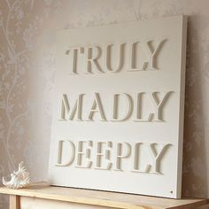 Wooden letters painted the same colour as the canvas.... Simple, but great effect.
