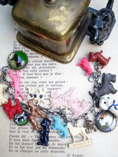 Vintage Dogs Charm Bracelet with Big Pink Scottie This one has 18 different, vintage dog charms including celluloid, metal, glass cabochons. All the charms are vintage and special and many breeds are represented including: Airdales, mutts, Poodles, Dachshunds, Spaniels, Boxers and more! In the center is a big pink Scottish Terrier!...