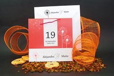 Sencilla invitación de boda realizada en cartulina mate blanca, con una gran solapa en color rojo, con dos flores de diente de león impresas en blanco.Presenta como detalle decorativo una etiqueta con los datos del enlace y unida a la solapa por un fino lazo de ante a juego.