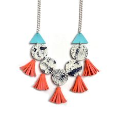 This handmade leather necklace features hand painted details with a unique fringe style. Hand cut with love, hand cut white leather circles with a marbled black