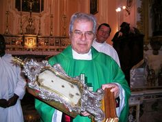 Another Priest carrying the Eucharistic Miracle of Bagno di Romagna-1412: Holy Mass was seized by the doubt about the real presence of the body and blood of Christ in the Eucharist: drops of blood, as seething with life, spilled from the chalice on the corporal pouring, which is soaked. The miracle is known to us from the story of Abbot Benedict Tenacious who wrote in his diary. The Sacred Corporal bears eight imprinted bloodstains