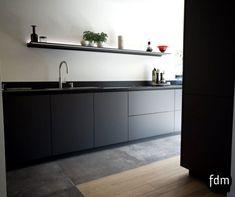 Deze grijze op maat gemaakte moderne, strakke, greeploze keuken, is mooi afgewerkt met hoge kasten, een granieten aanrechtblad en wandschap met geïntegreerde verlichting. Dit wandschap komt van Dekker Zevenhuizen.