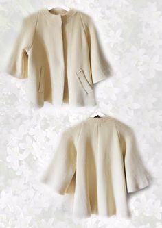 Collezione Yoko    Cappotto forma trapezio con maniche a kimono, manica raglan, tasche  Maglieria tagliata a coste in rilievo fin.5,foderato in seta con passamaneria applicata  Col. Crema  100%CO  TG.44/46  Prezzo 360,00 euro  Ph Benedetta Balloni