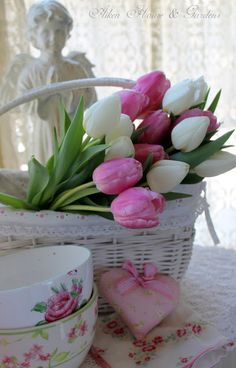 Praying angel, pink and white tulips in white basket, painted teacups