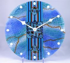 """This elegant beautiful wall clock (D=12"""") is a combination of various lines and dots mixed with fantastic """"elf"""" symbols in the center. In general this clock looks similar to the Rectangular platter with the same name. Besides the beauty of this clock it has one very important feature: It's a set-and-forget clock. It knows when to switch daytime savings time and does it automatically.  which is done by using 3 different techniques:  -The square in the center is a combination of small…"""